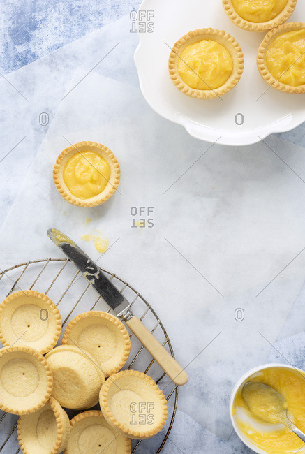 Unfilled pastry cases on a wire rack and lemon tartlets on a plate.