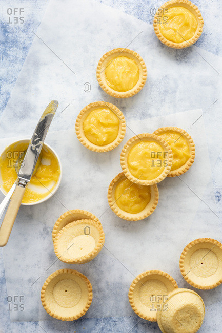 Empty and filled lemon tartlets with a bowl of lemon curd and a knife.