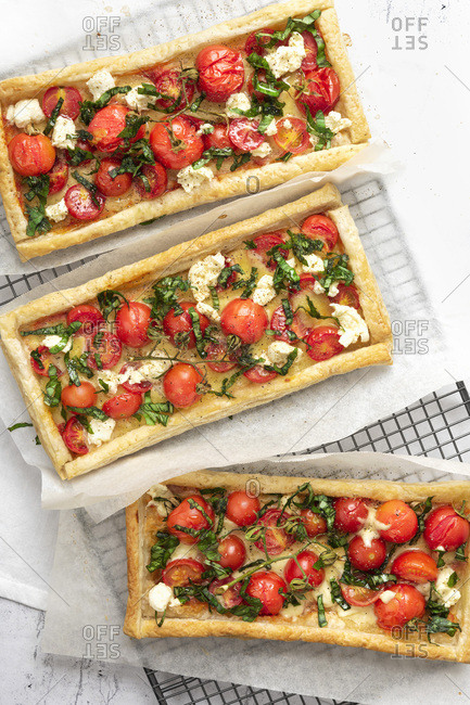 Three rectangular bocconcini, tomato and basil tarts on baking paper.