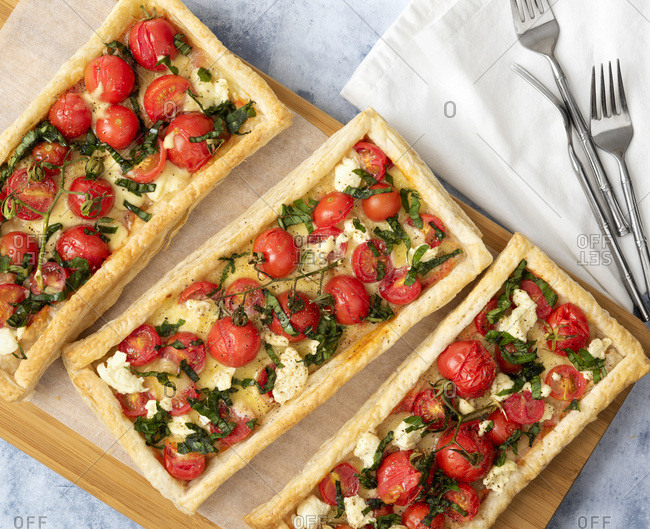 Three bocconcini, tomato and basil tarts on a wooden serving board with forks.