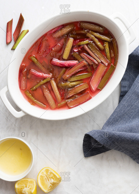 Cooked rhubarb with lemon in a white oval serving dish.
