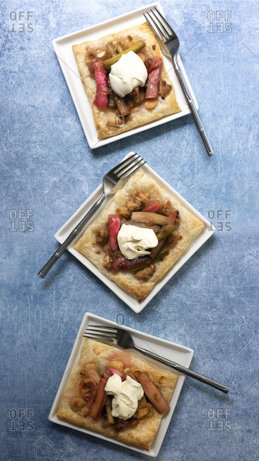 Three individual rhubarb and almond tarts with forks on a textured blue background.
