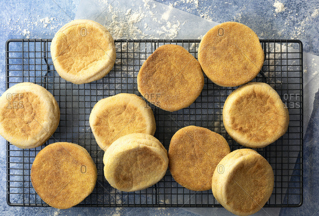 Cooked English muffins cooling on a wire rack.