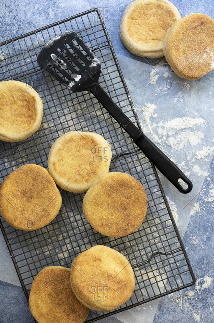 English muffins cooling on a wire rack with a lifter.