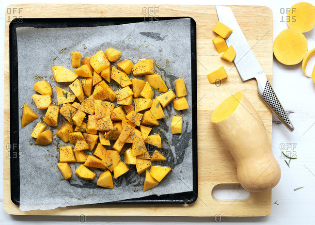 Pieces of raw butternut seasoned with herbs and coated in oil on a baking tray with a knife.