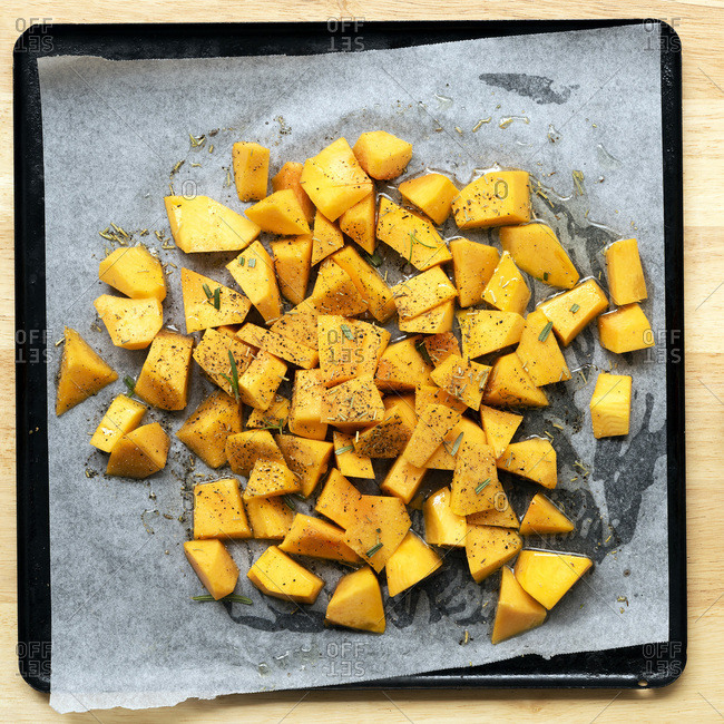 Small pieces on butternut coated in oil and seasoning on a baking tray.