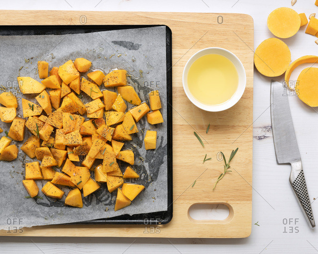 Small pieces on butternut on a baking tray with a bowl of oil and a knife.