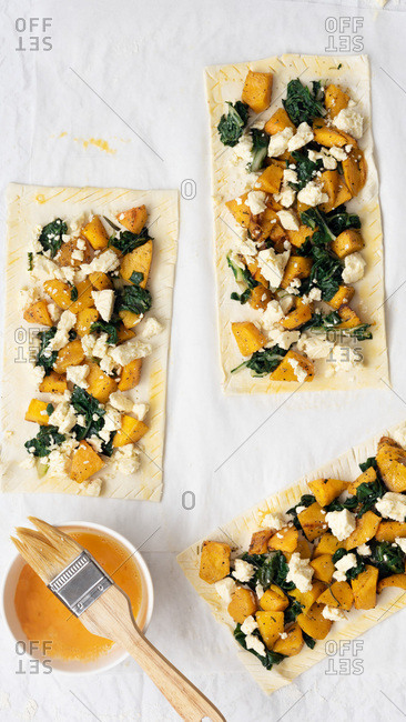 Three uncooked roast pumpkin, spinach and feta cheese tarts with a pastry brush and bowl of egg yolk.