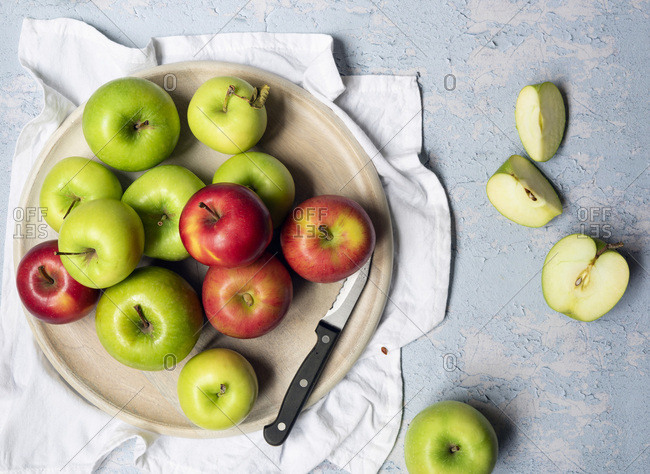 Green cooking apples and red eating apples with a knife on a round wooden board.
