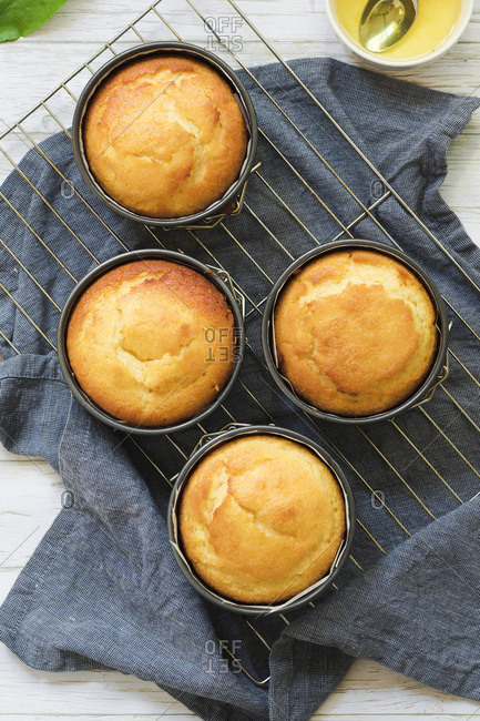 Small round individual orange cakes cooling in cake tins on a wire rack and blue cloth napkin.