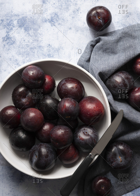 A bowl of ripe red plums and a knife with scattered plums on a blue napkin.