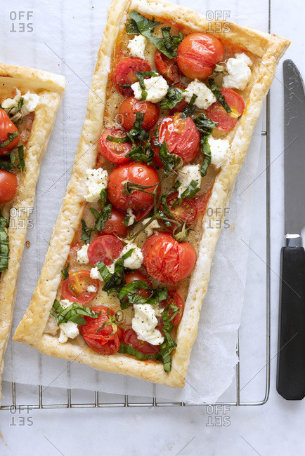Rectangular savory tart filled with cherry tomatoes, feta cheese and chopped basil leaves.