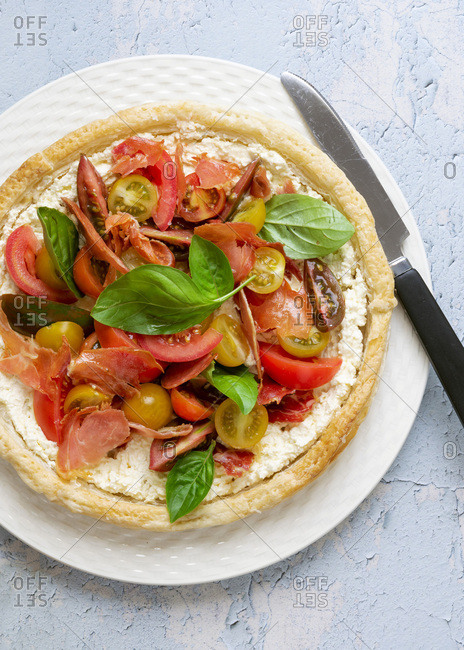 Round savory tart filled with feta cheese, pancetta, tomatoes and basil leaves on a plate with a knife.