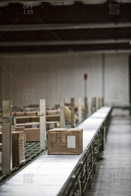 Interior view of a large distribution warehouse showing a motorized conveyor system to move products stored in cardboard boxes