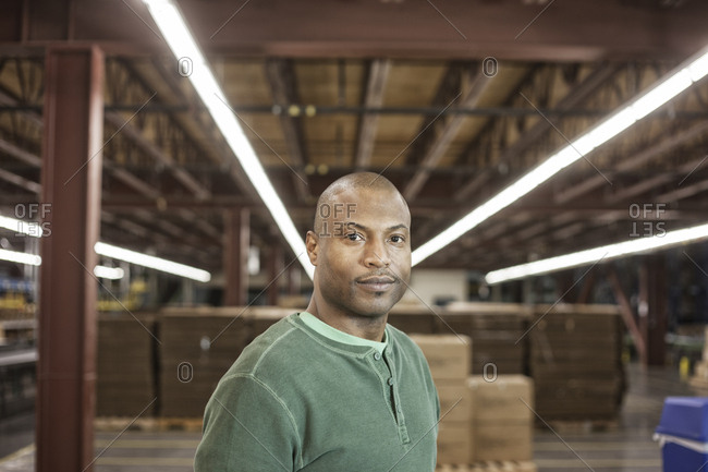 Working portrait of an African American warehouse worker in a large distribution warehouse