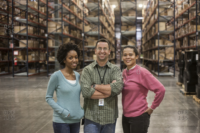 Team portrait of three  male and female multi-ethnic warehouse workers in a large distribution warehouse with products stored in cardboard boxes on pallets and on large racks in the background