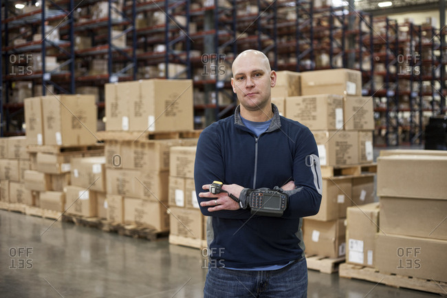 Portrait of a Caucasian warehouse worker in a large distribution warehouse, showing products stored in cardboard boxes