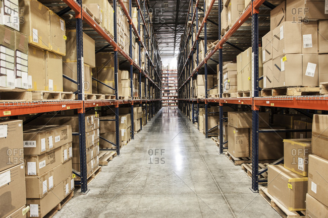 View down an aisle of racks holding cardboard boxes of product on pallets  in a large distribution warehouse
