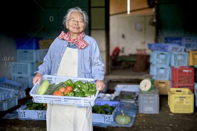 Elderly woman with grey hair standing in front of barn, holding blue plastic crate with fresh vegetables, smiling at camera