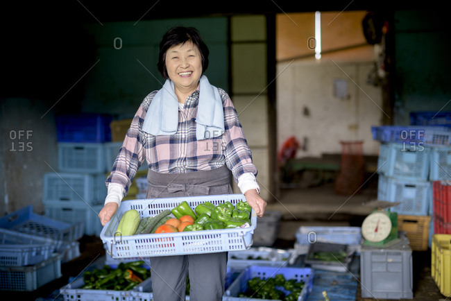 Woman with black hair wearing checkered shirt standing in front of barn, holding blue plastic crate with fresh vegetables, smiling at camera