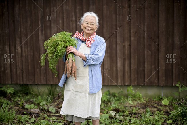 Elderly woman with grey hair standing in a garden, holding bunch of fresh carrots, smiling at camera