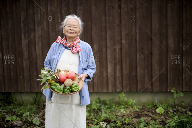 Elderly woman with grey hair standing in a garden, holding a basket with fresh vegetables, smiling at camera