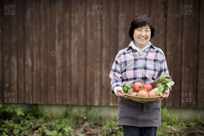 Woman with black hair wearing checkered shirt standing in a garden, holding basket with fresh vegetables, smiling at camera