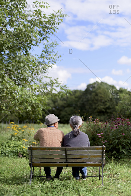Husband and wife, rear view of elderly man wearing hat and woman sitting side by side on a bench in a garden