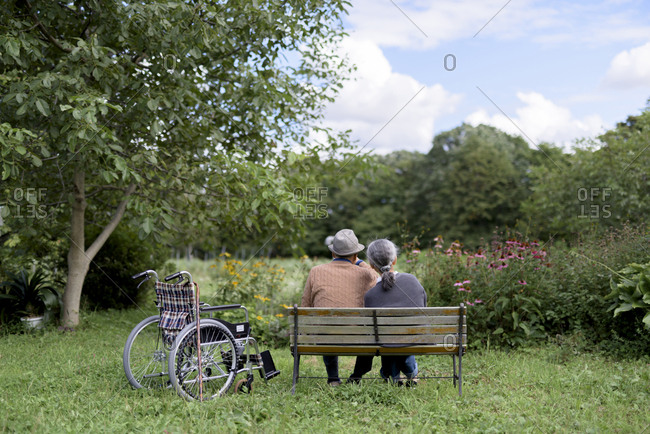 Husband and wife, rear view of elderly man wearing hat and woman sitting side by side on a bench in a garden with wheelchair parked alongside