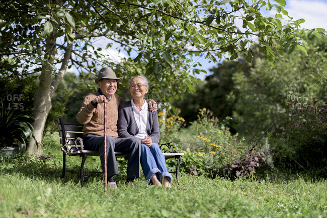 Husband and wife, elderly man wearing hat and woman sitting side by side on a bench in a garden