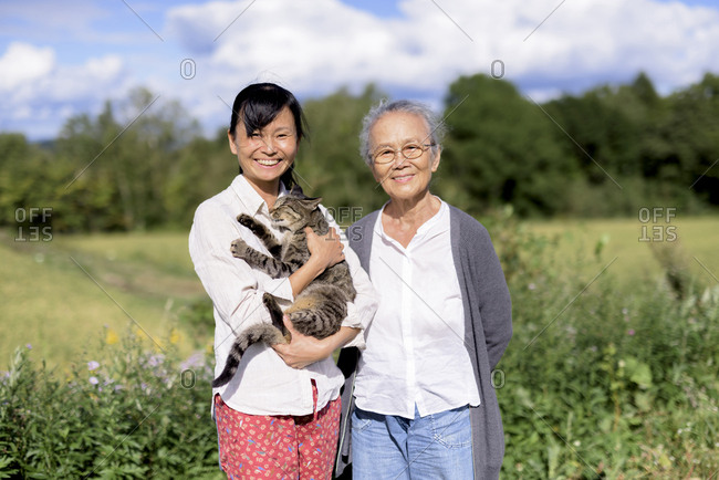 Smiling woman holding grey cat standing outdoors, with an elderly woman, smiling at the camera
