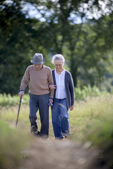 Husband and wife, elderly man wearing hat and using walking stick and elderly woman walking along path