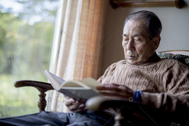 Elderly man sitting in rocking chair by a window, reading book