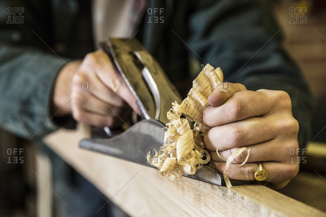 Close up of man working standing in a woodworking workshop, using plane on plank of wood