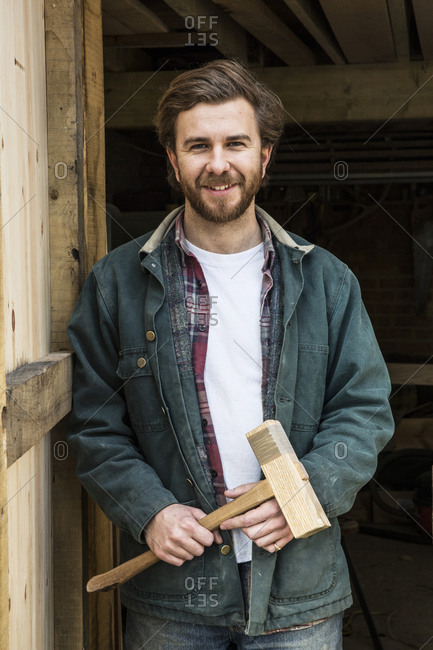 Bearded man standing in doorway of woodworking workshop, holding wooden mallet, smiling at camera