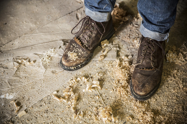 High angle view of a man wearing jeans and brown leather boots standing in a workshop, wood shavings on the floor