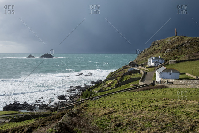 Cot Valley, St Just, West Cornwall coastline View of cottages overlooking the coast and the Brisons Rocks under a darkening stormy sky