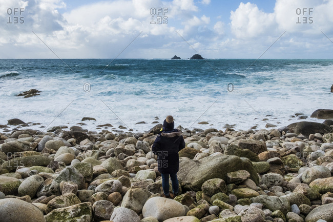 A woman standing on the rocks looking out over the Cornish coastline, and breaking waves