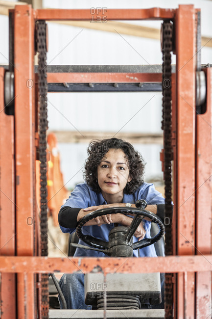 Hispanic woman employee using a forklift in a landscape company