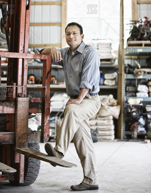 Hispanic man owner of a landscape company standing in the equipment room