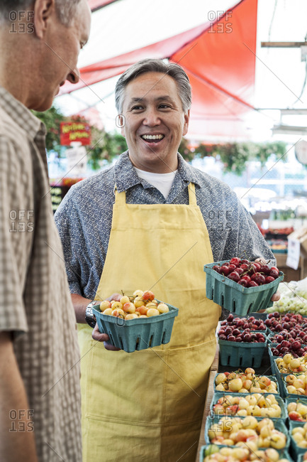 Man wearing apron standing at stall with punnets of fresh cherries at a fruit and vegetable market, chatting with customer