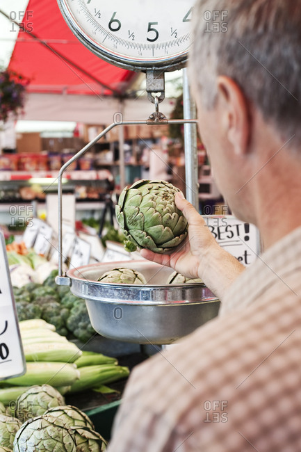 Over the shoulder view of man weighing artichoke at a fruit and vegetable market