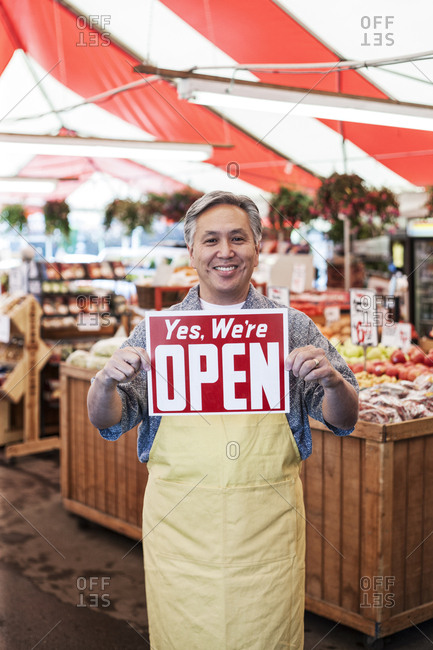 Smiling man wearing apron at a fruit and vegetable market, holding aloft Open sign