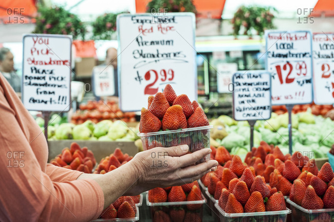 Close up of person holding punnet of fresh strawberries at a fruit and vegetable market