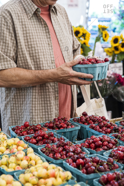 Man standing at stall, holding punnet with fresh cherries at a fruit and vegetable market