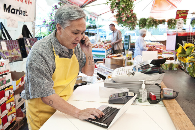 Man wearing apron standing at the checkout of a food and vegetable market, on the phone, typing on laptop computer