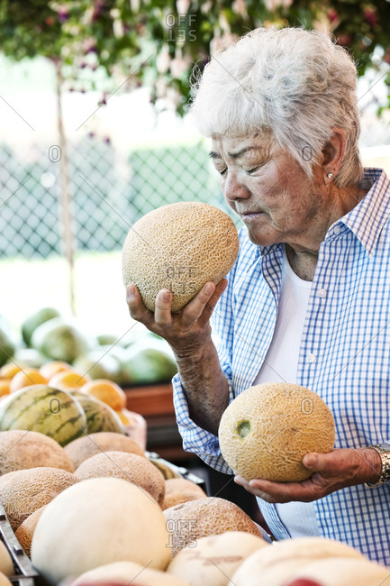 Senior woman standing at a farm stall, holding a fresh melon to her nose, smelling it