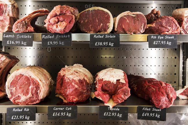 Close up of selection of cuts of lamb and beef on metal shelves in butcher shop