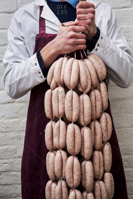 Man wearing apron holding large number of freshly made sausages hanging from hooks