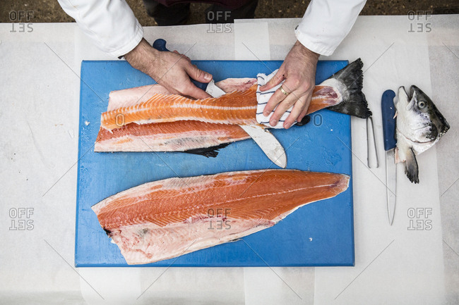 High angle close up of fishmonger standing at a table, cutting and filleting fresh salmon on blue chopping board